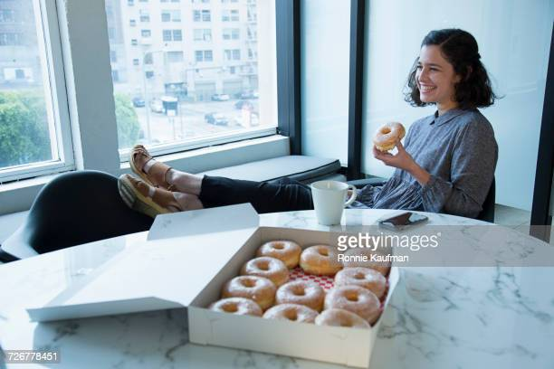 businesswoman eating donut in conference room - dozen stock pictures, royalty-free photos & images