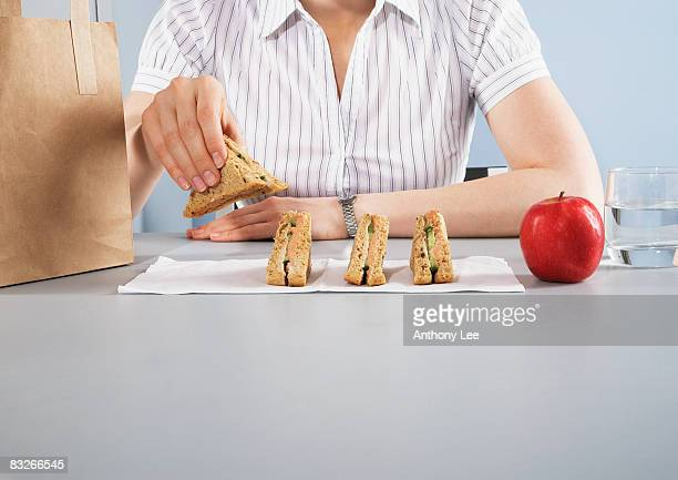 Businesswoman eating healthy lunch at desk