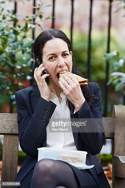 Businesswoman eating lunch and talking on phone