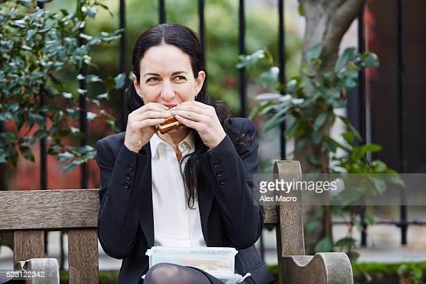 Businesswoman eating lunch and texting