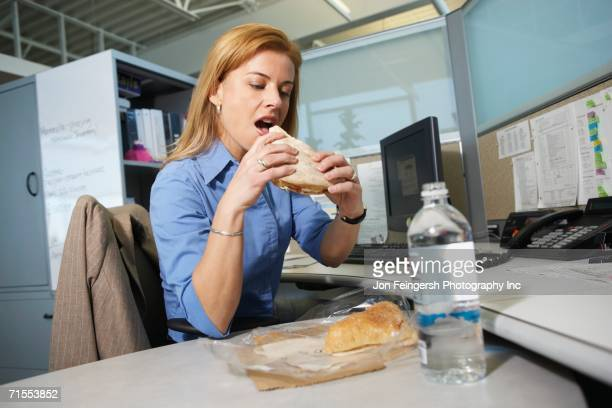 Businesswoman eating lunch at desk