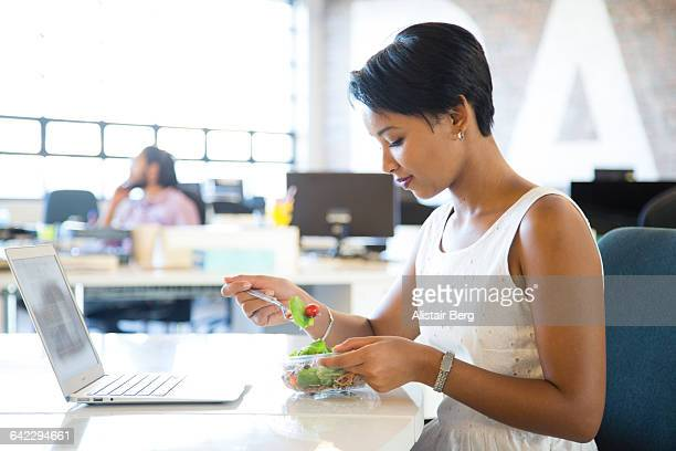 Businesswoman eating lunch in  an open plan office