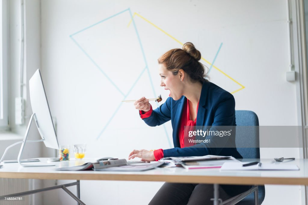 Businesswoman eating lunch in office : Stock Photo