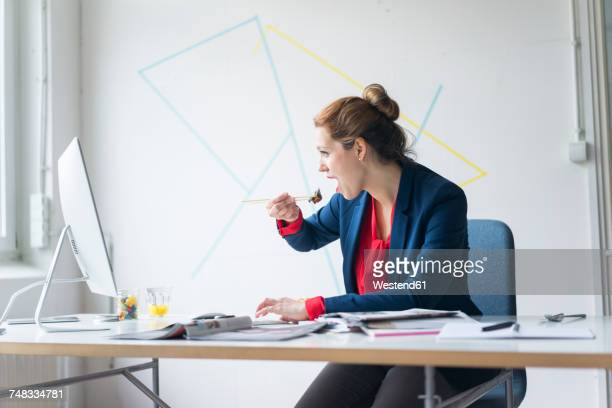 businesswoman eating lunch in office - unhealthy living stock pictures, royalty-free photos & images