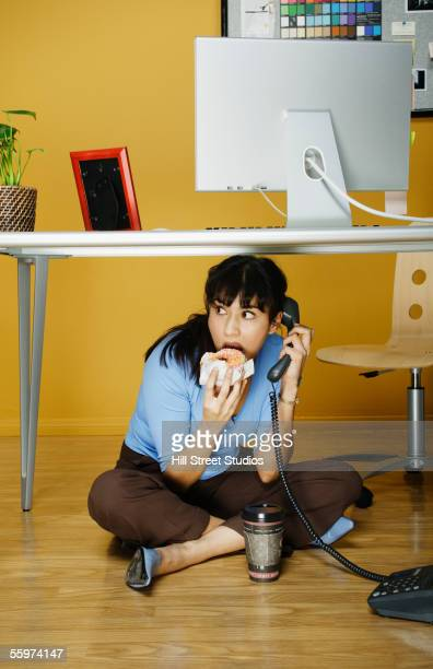 Businesswoman eating lunch under desk