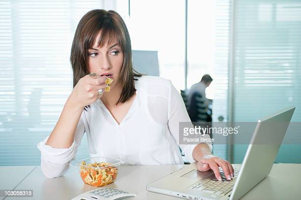 Businesswoman eating pasta and using a laptop