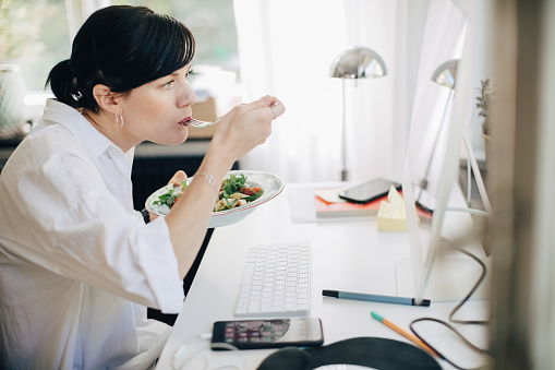 Businesswoman eating pasta while looking at computer in home office. - gettyimageskorea