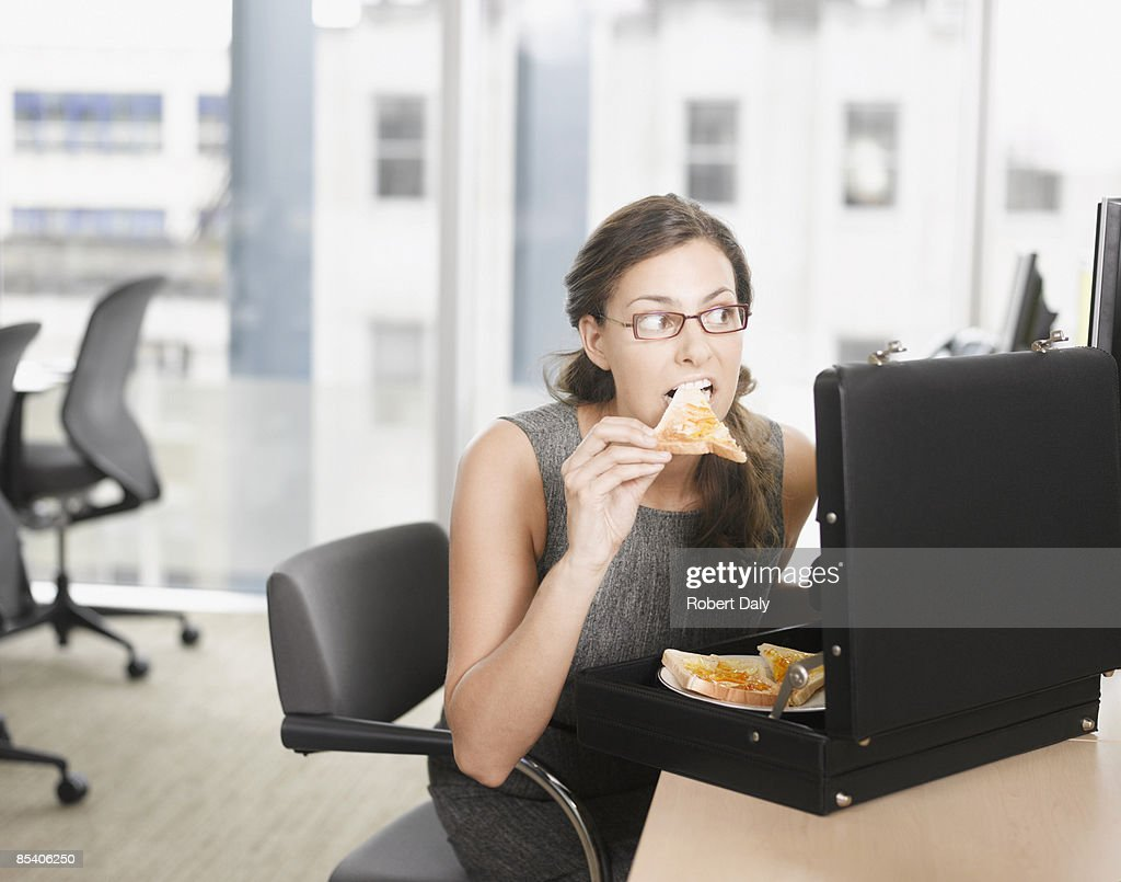 Businesswoman eating pizza from briefcase : Stock Photo