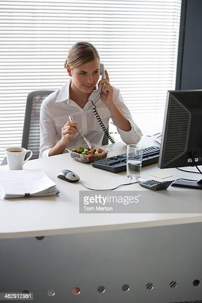 Geschäftsfrau Essen Salat und Gespräch am Telefon am Schreibtisch