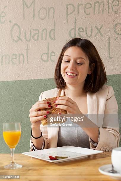 businesswoman eating sandwich in cafe - stefanie grewel stock-fotos und bilder