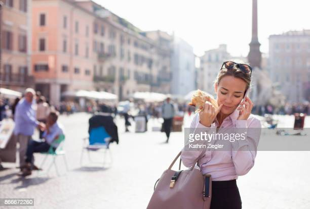 Businesswoman eating sandwich on the go while talking on mobile phone, Rome, Italy