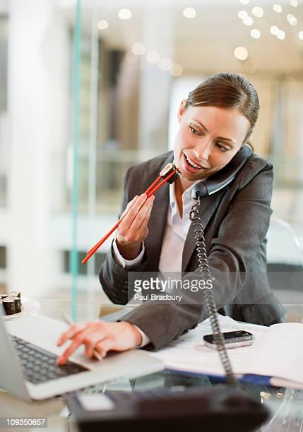 Geschäftsfrau Essen sushi und Arbeiten am Schreibtisch