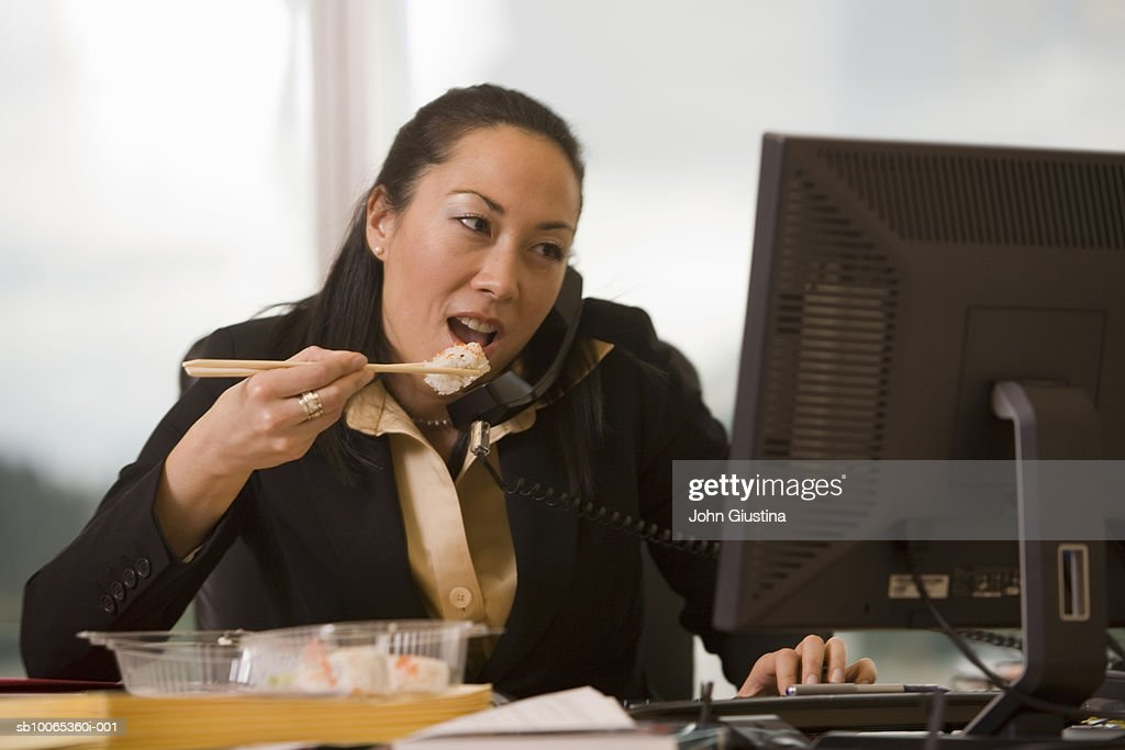 Businesswoman eating sushi at desk using computer : Foto stock