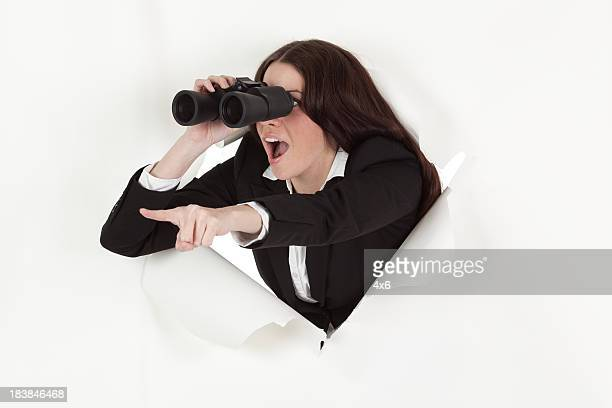 Businesswoman emerging through hole using binoculars