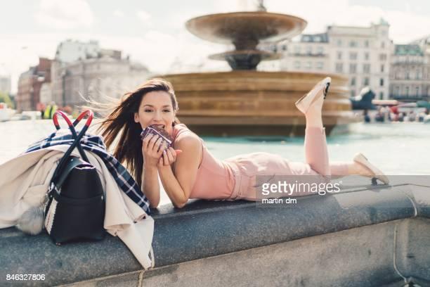 Businesswoman enjoying a chocolate bar at the fountain