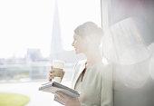 Businesswoman enjoying cup of coffee at window