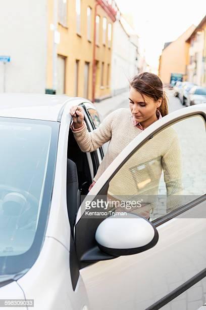 Businesswoman entering car on street