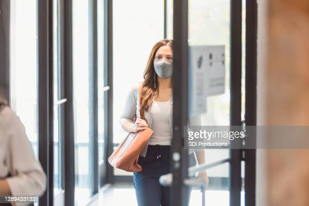 businesswoman enters office during covid-19 - returning stock pictures, royalty-free photos & images
