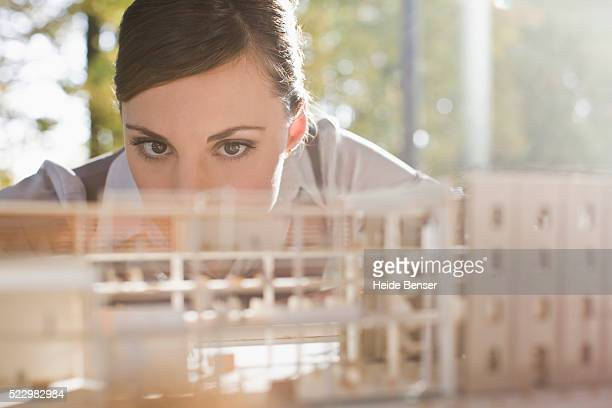 businesswoman examining architectural model - architectural model stock pictures, royalty-free photos & images