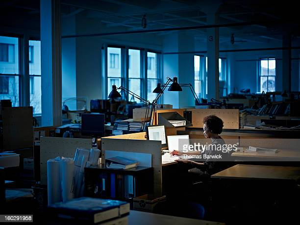 businesswoman examining documents at desk at night - 精神統一 ストックフォトと画像