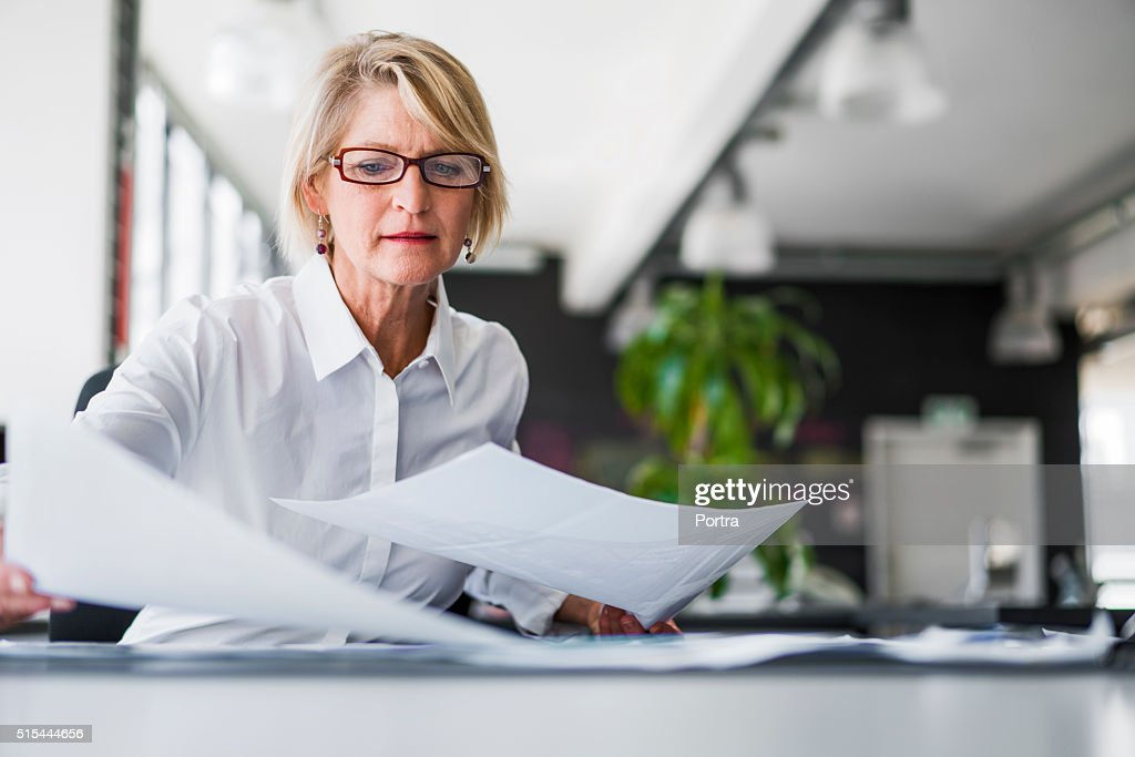 Businesswoman examining documents at desk : Stock Photo