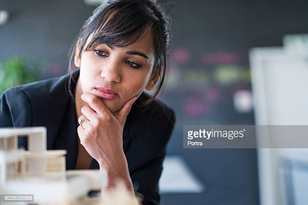 Businesswoman examining model at workplace