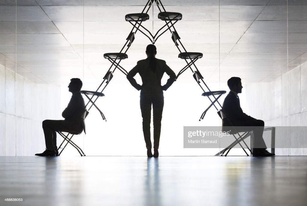 Businesswoman examining office chair installation art : Stock Photo