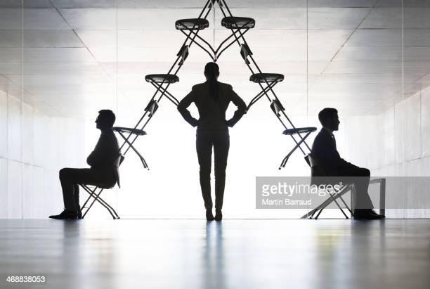 Empresaria examinar silla de oficina instalación artística
