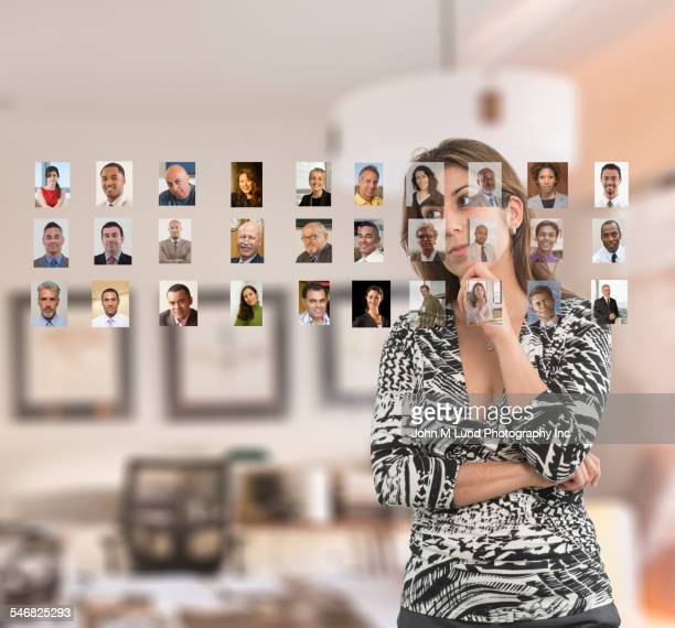 businesswoman examining photos of colleagues on touch screen - internet dating stock pictures, royalty-free photos & images