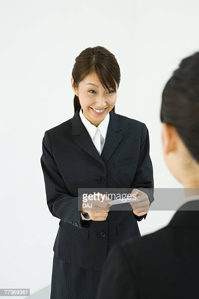 Businesswoman Exchanging Business Cards, Smiling, Three Quarter Length, Front View, Rear View