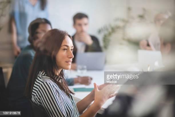 businesswoman explaining colleagues during brainstorming session in creative office - begrippen en thema's stockfoto's en -beelden