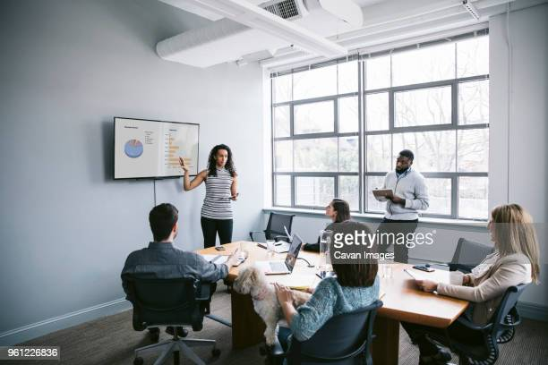 businesswoman explaining data to colleagues in meeting at board room - one animal stock pictures, royalty-free photos & images