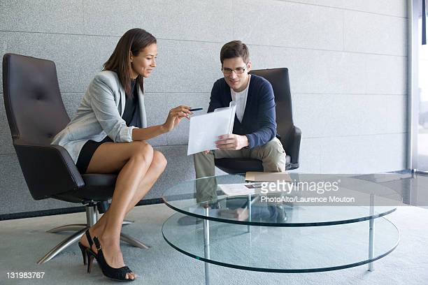Businesswoman explaining document to client