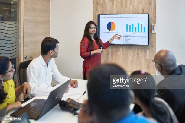 businesswoman explaining graph to colleagues - entrepreneur stock pictures, royalty-free photos & images