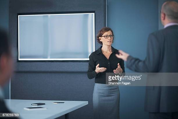 businesswoman explaining ideas with colleague - older women in short skirts stock pictures, royalty-free photos & images