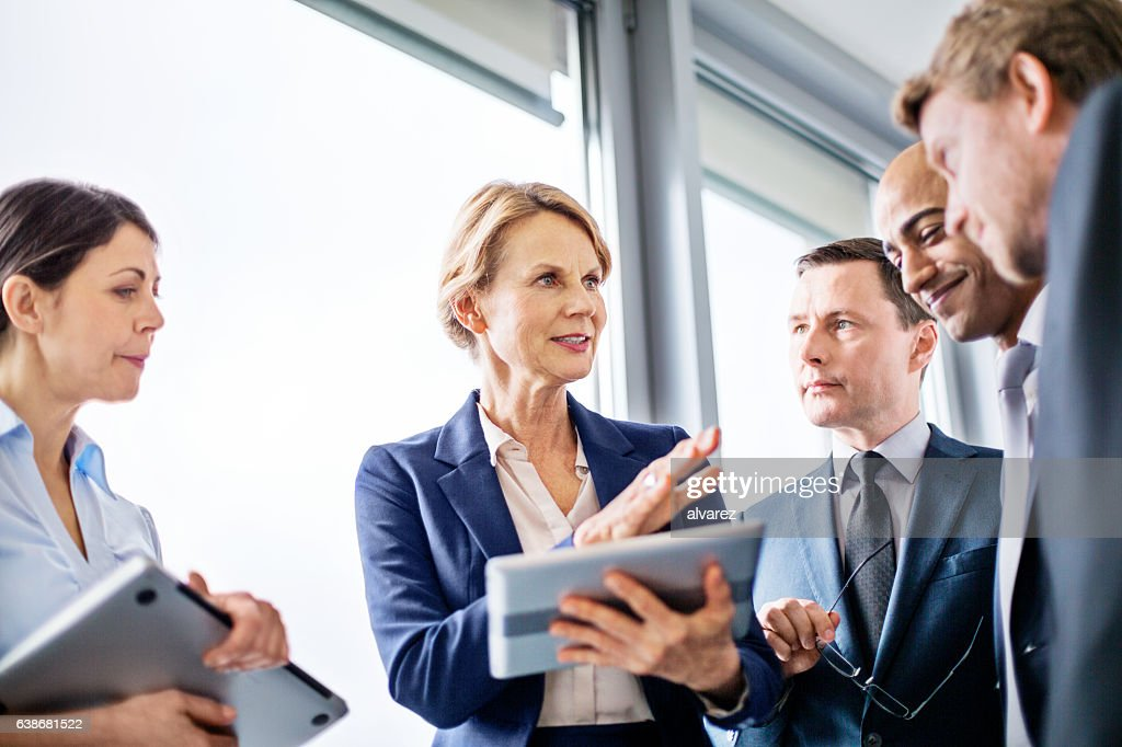 Businesswoman explaining new business ideas to colleagues : Stock-Foto