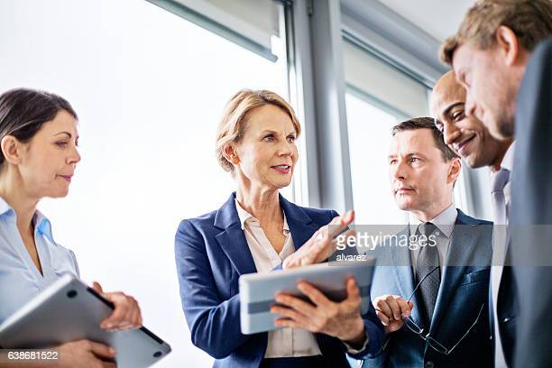 businesswoman explaining new business ideas to colleagues - sharing stock photos and pictures
