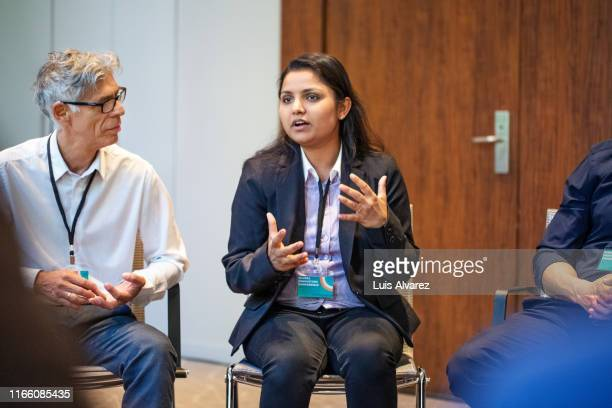 businesswoman explaining new ideas to professionals - panel discussion stock pictures, royalty-free photos & images