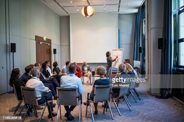 businesswoman explaining strategy over a flip chart - werkstatt stock-fotos und bilder