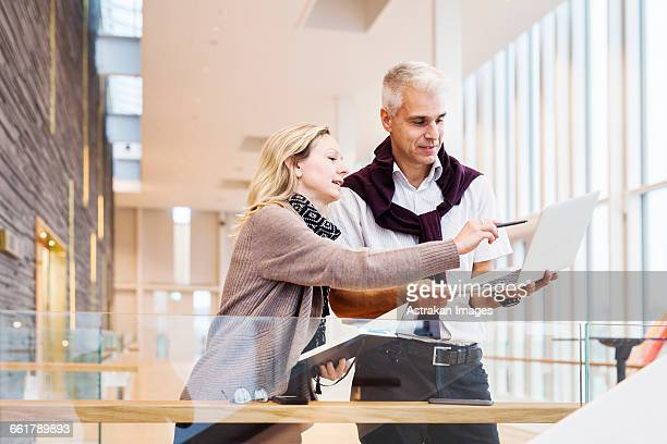 Businesswoman explaining strategy to colleague on laptop at hotel lobby