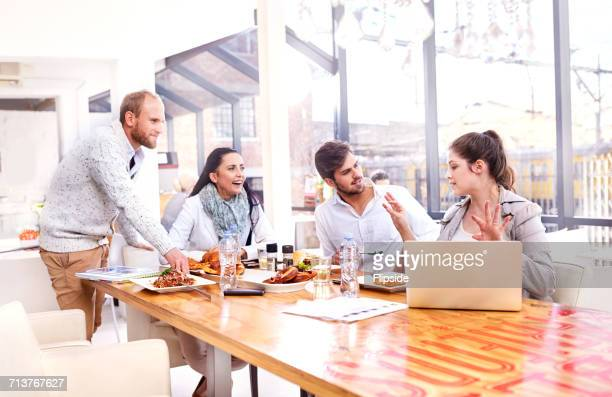 businesswoman explaining to business team during working lunch in restaurant - smart casual stock pictures, royalty-free photos & images