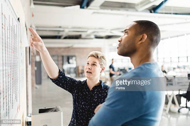 Businesswoman explaining to colleague on whiteboard