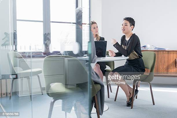 Businesswoman explaining to colleagues behind glass partition
