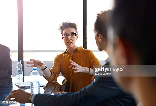 businesswoman explaining to coworkers at meeting - gesturing stock pictures, royalty-free photos & images