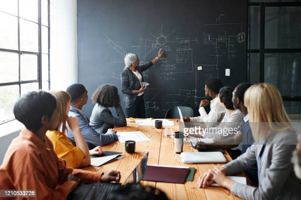 businesswoman explaining to coworkers in meeting - employee engagement stock pictures, royalty-free photos & images
