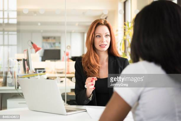 Businesswoman explaining to female colleague, gesturing with hand