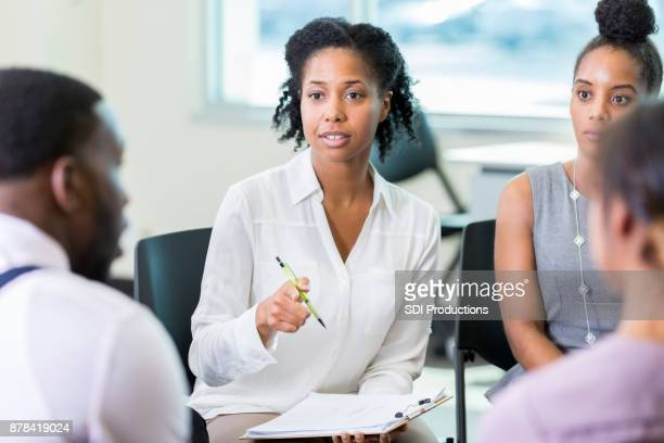 businesswoman facilitates meeting - psychologist stock photos and pictures