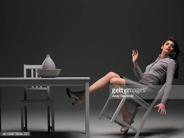 businesswoman falling down from chair, side view - 不均衡 ストックフォトと画像