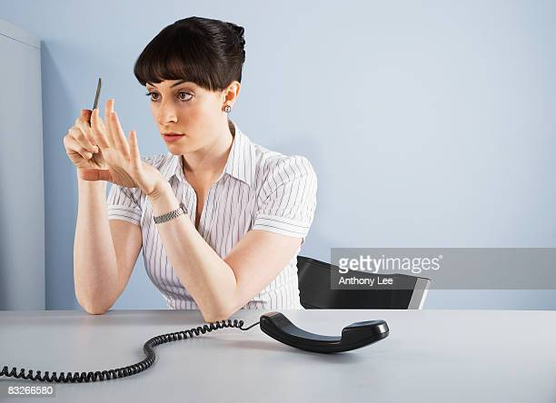 Businesswoman filing fingernails and ignoring telephone call