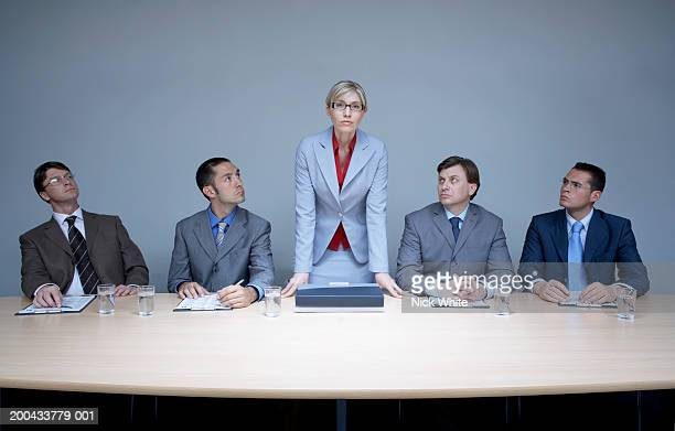 Businesswoman flanked by businessmen standing up from boardroom table